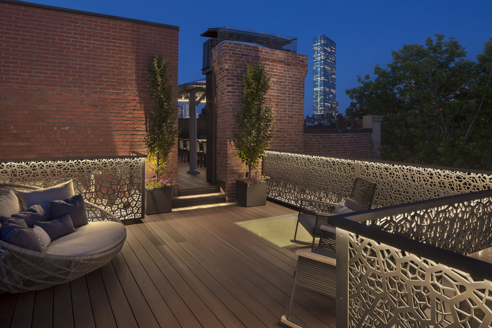 The railings help screen roof utilities and define this seating area.