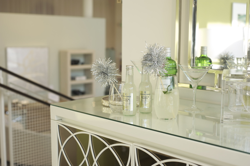 Serve up summer cocktails on their white lacquered wood andbronze mirrored Lawson Bar.