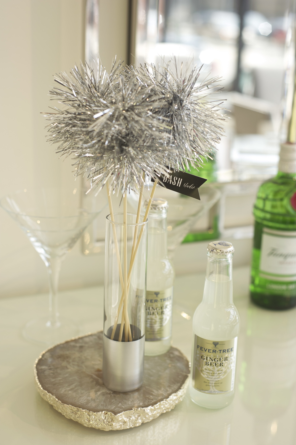We created simple tall glass vessels for the drink stirrers that looked like they were dipped in silver by simply taping off the top and spray painting the bottom.