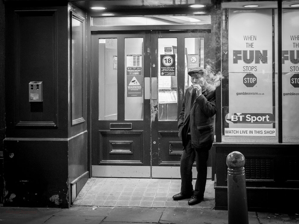 A dark scene featuring a man smoking (the smoke is obvious) leaning against the front of a betting shop (bookies as we say in the UK). The text reads 'When the Fun Stops, Stop'. Camera: Olympus OM-D E-M1. Lens: 12-40mm f/2.8 PRO @ Aperture: f/2.8 Focal Length 12mm ISO: 3200 Shutter Speed: 1/80th
