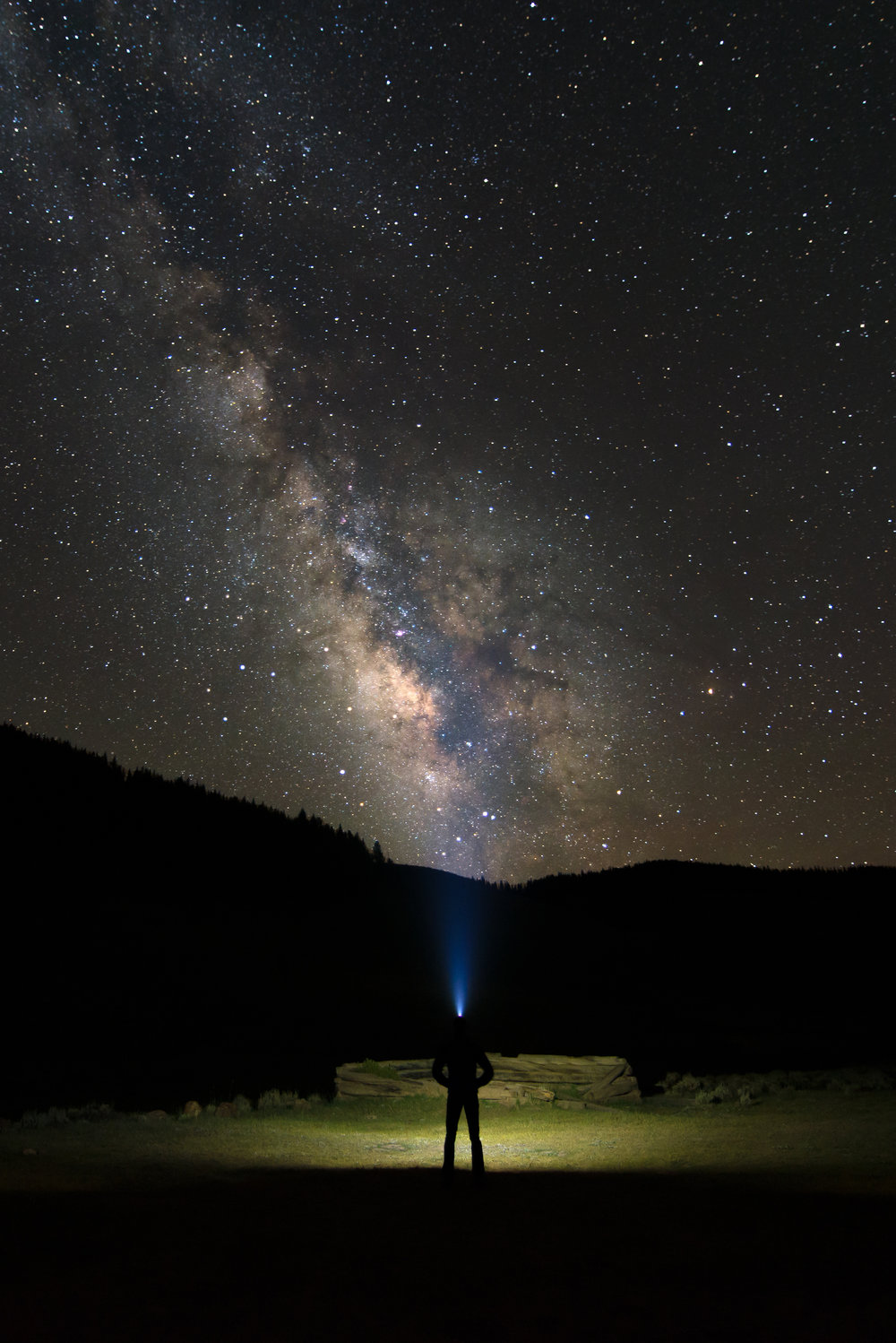 A lone camper watches the Milky Way set over their campsite