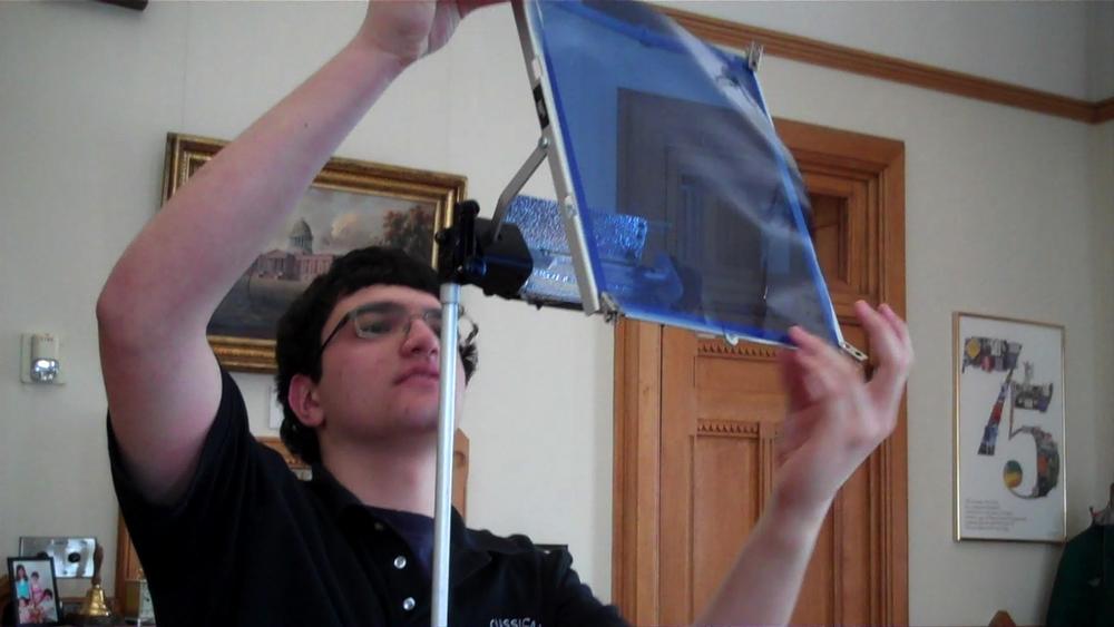 Ben McGowan hangs a blue gel. The blue gel makes artificial light look more like sunlight on camera.