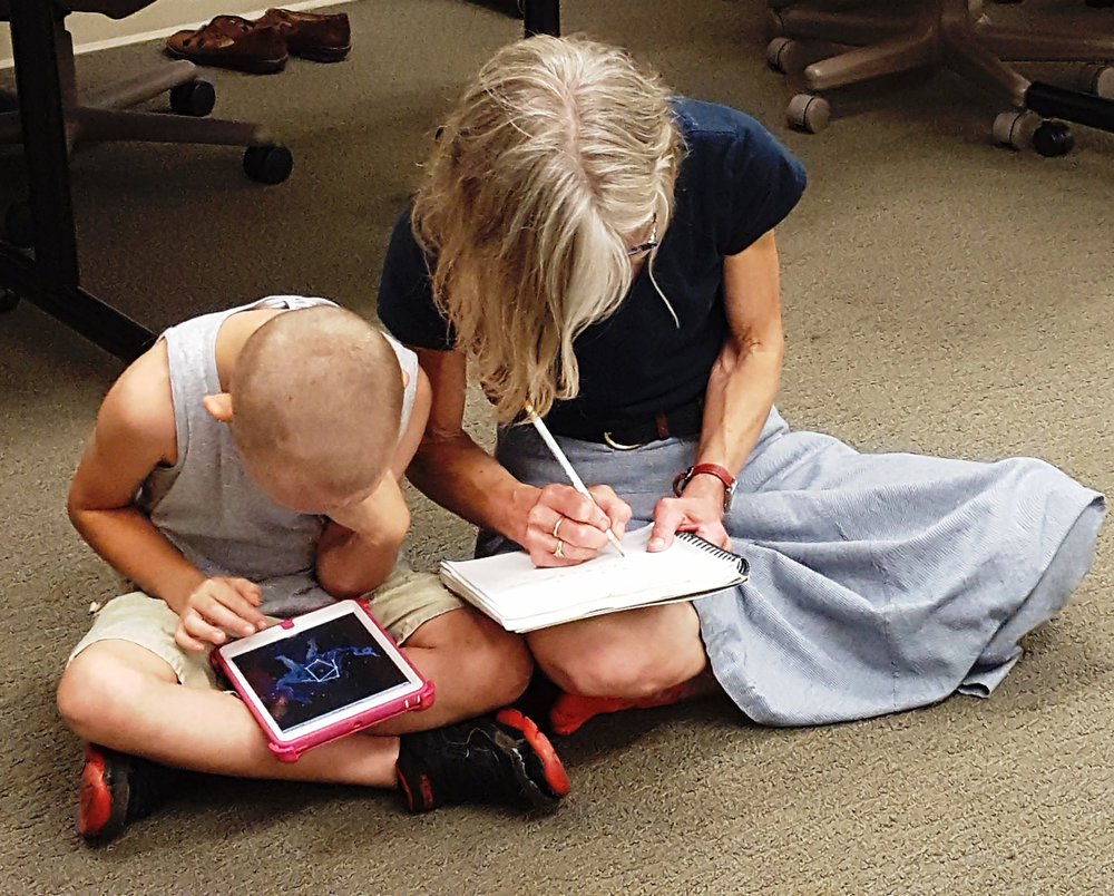 at Early Connections, Bailey creates a constellation on the Christopher counts the constellation iPad® app while dictating his story to Mary.