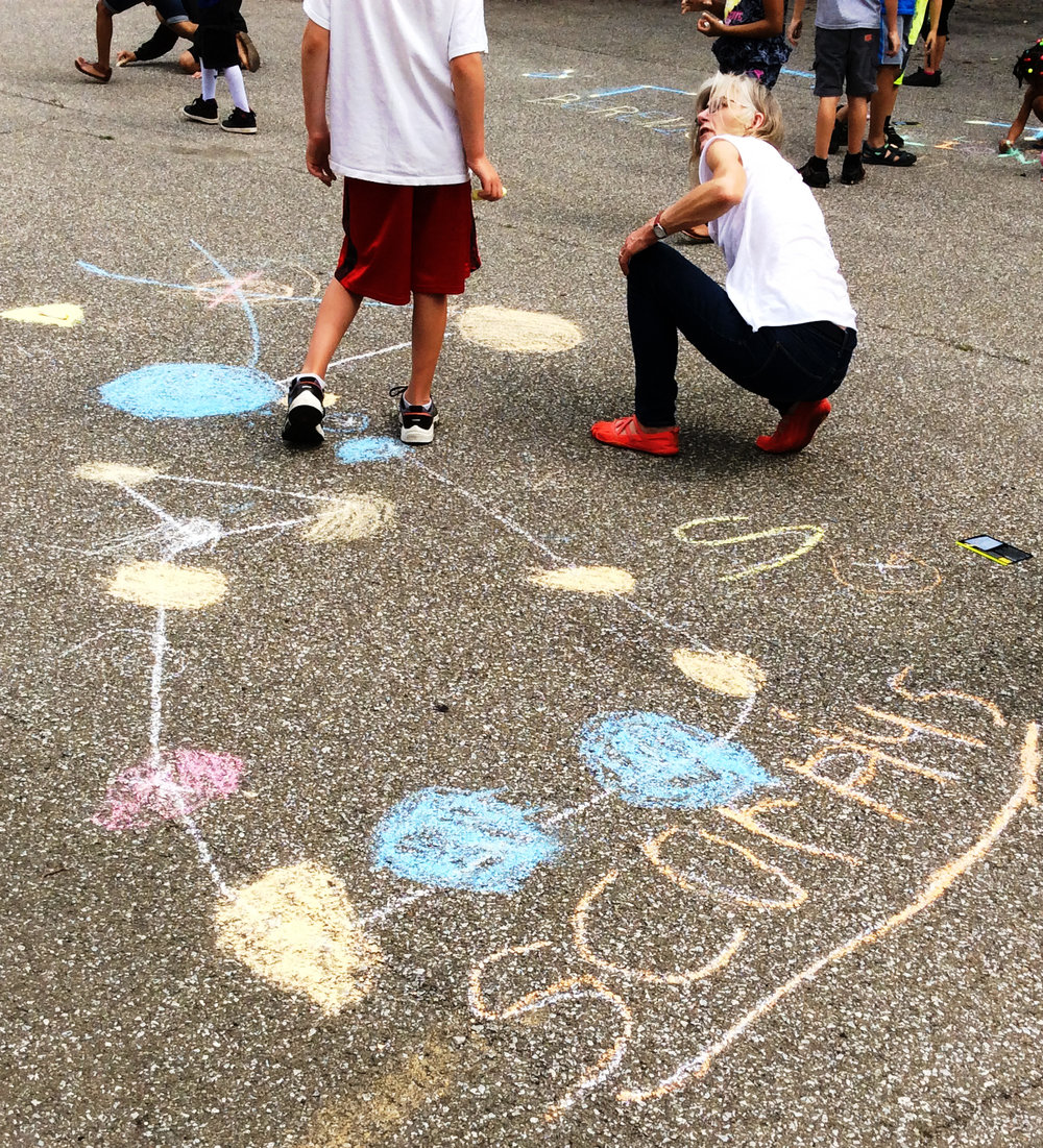 Early Connections children use sidewalk chalk to draw stars by cars.