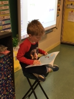 1st grader reads When the Camel Sneezed to classmates.