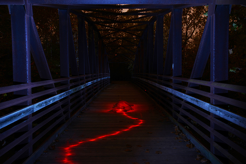 Matt McCormack lies in the middle of a bridge at Capen Park Tuesday evening October 21, 2014. The bridge is lit up using pops of an off-camera flash using a blue gel. Matt is lit with a flash light with a red gel.