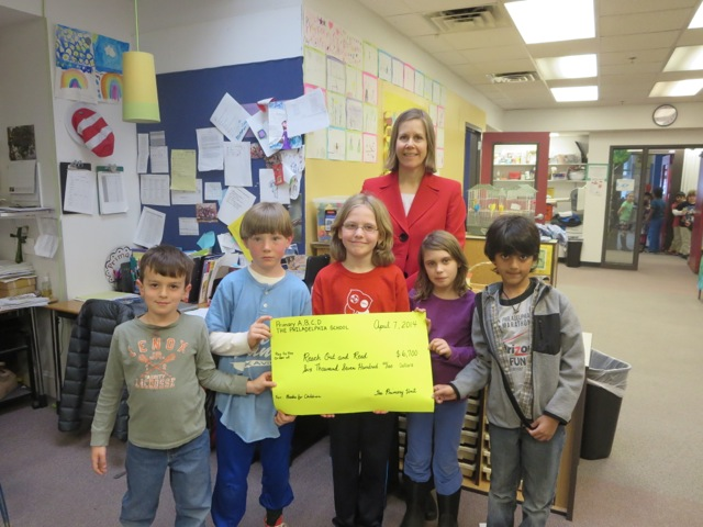 "Students present a ""check"" to a representative from Reach Out and Read."