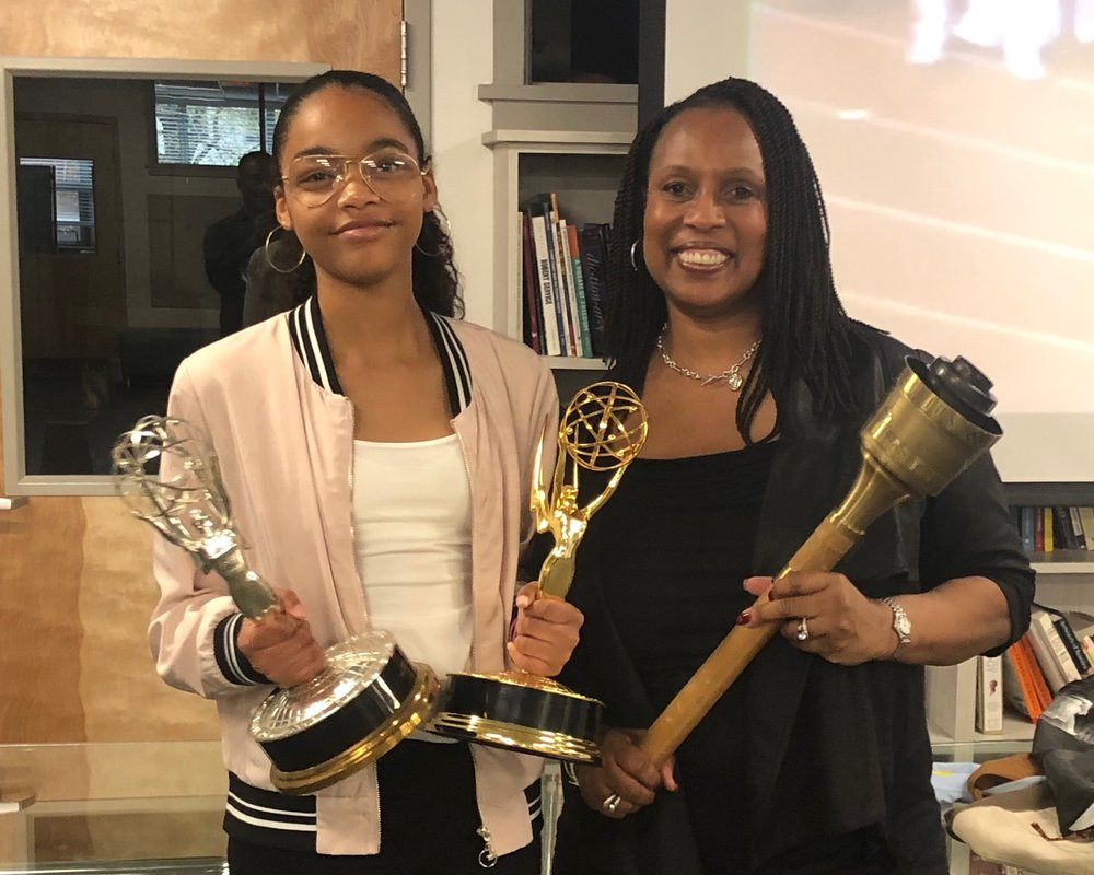 Jade and Gina holding the Olympic torch that Gina carried and two of her Emmy Awards.