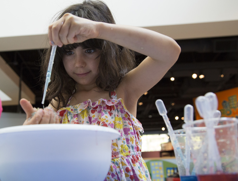 Chloe Wolf, 7, plays with polymers at Marbles Kids Museum Sunday .