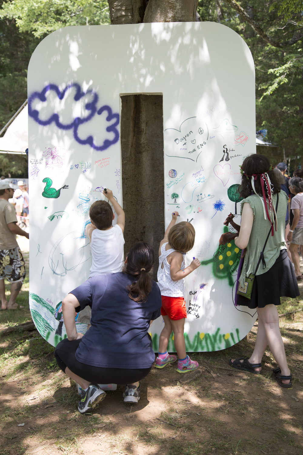 "Festival goers add artwork to the giant ""O"" near the Meadow stage at the Festival for the Eno in Durham on Friday, July 4, 2014. There was also a ""E"" and ""N"" near the stage."