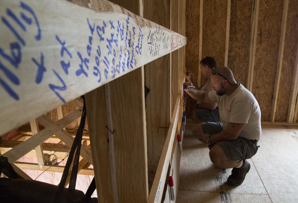 Wednesday: Jason McIntyre writes a note of thanks in the unfinished attic of the future home of Corporal Nathan Jakubisin in Fuquay-Varina, N.C., Wednesday, July 9, 2014. Nearly a hundred people wrote messages of gratitude, pride or encouragement on the wooden frames in the unfinished attic. The construction is a collaboration of the Home Builders Association of Raleigh-Wake and Operation: Coming Home, an organization that provides new, mortgage-free homes for wounded veterans. Jakubisin suffered severe leg and hand injuries from an improvised explosive device in Afghanistan in 2012.