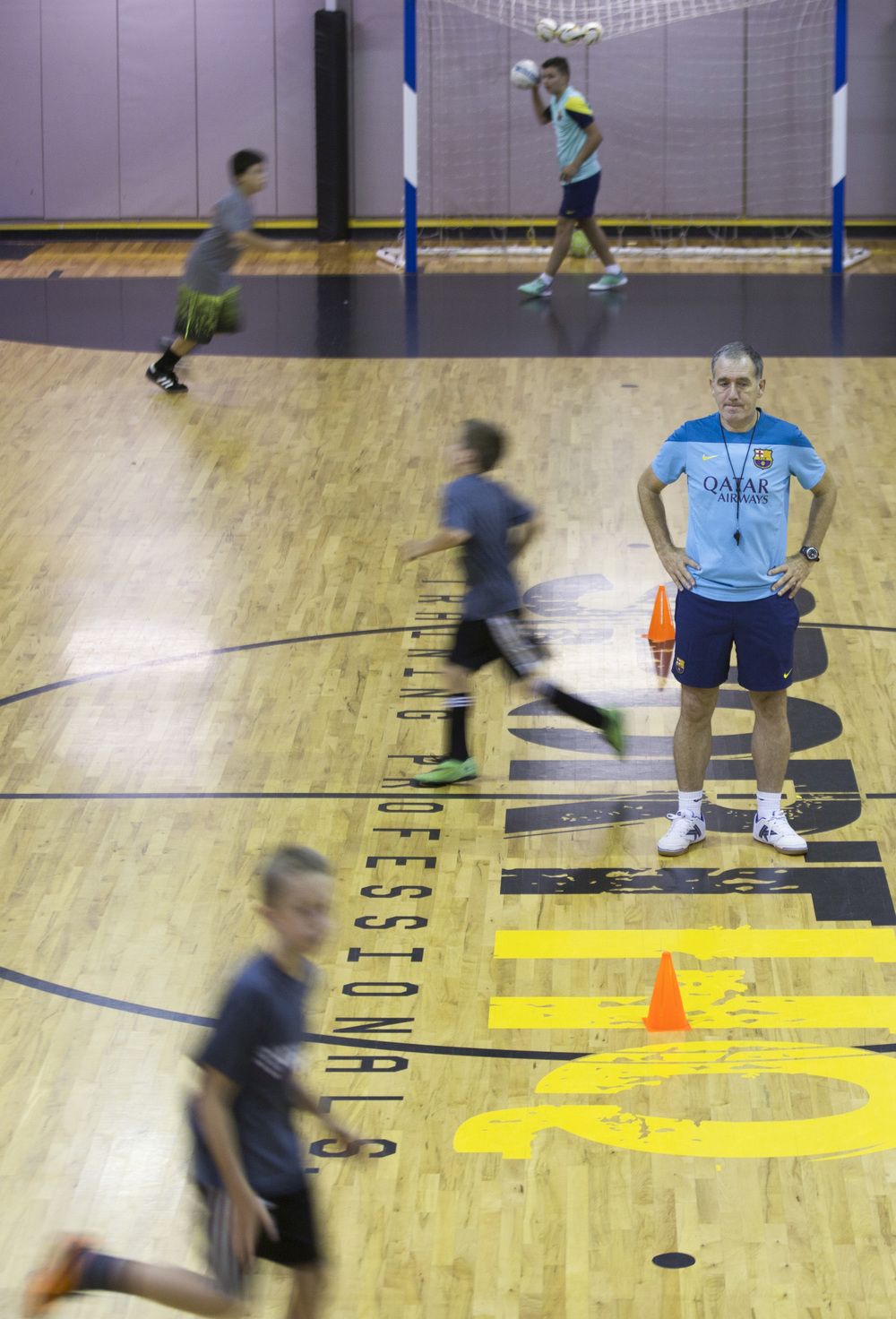 "After feature hunting I was sent to a gym in Cary to watch futsal, a type of indoor soccer. I can't express how much I hate bad gym lighting.  Coach Andreu Plaza coaches campers at the Futsal Academy at SportHQ in Cary, N.C., Thursday July 10, 2014. Plaza travelled from Barcelona, where he is coach of the Barcelona ""B"" Team and heads the FC Barcelona Youth Academy, one of the best youth futsal programs in the world. Futsal is like indoor soccer but allows players to play on gym floors rather than only on specially designed fields."