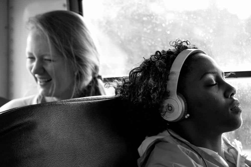 """It's always like this,"" said Jessica Willets. ""We are pumped when we get on the bus, but it quiets down as everyone starts to focus.""  Junior Josie Rouse jokes with fellow junior Lizzie Mann, while senior Dejah Cheatham listens to music to clear her mind."