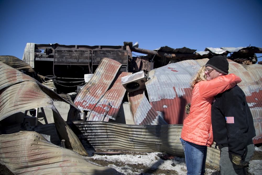 "Safety and Permits Compliance Officer Becky Eastman, of Fairlee, Vt., embraces Sawmill Dry Kiln Manager Tom Fulton, also of Fairlee, Vt., by the remains of the sawmill building at Britton Lumber Company in Fairlee, Vt., on Sunday, March 29, 2015. ""It's like losing a member of the family,"" Fulton said. A four-alarm fire leveled the building on Saturday night."