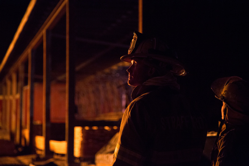 Strafford Fire Chief Jeremiah Linehan watches as firefighters from across the Upper Valley work to extinguish the four-alarm fire that leveled the sawmill building at Britton Lumber Company on Saturday, March 28, 2015.