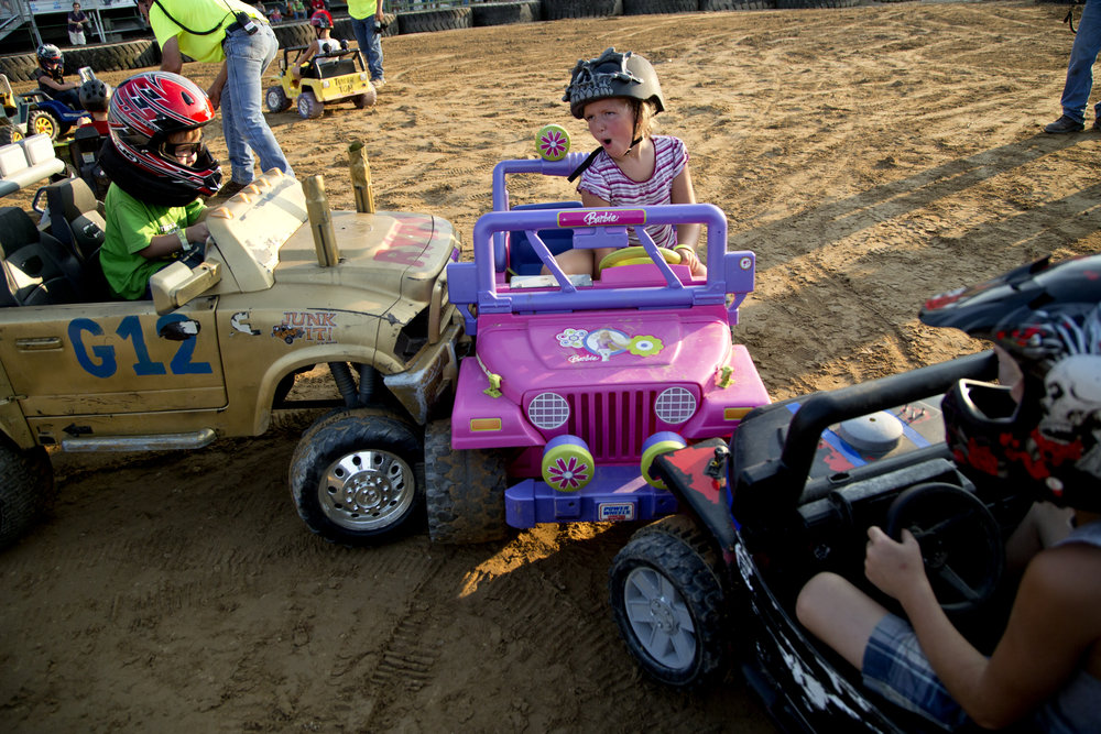 Abigail Conrad of French Lick, 6, reacted after being hit by Ryland Gerber of Winslow, 4, left, and Adam Onyette of Petersburg, 6, during the Power Wheels class of the demolition derby at the Dubois County 4-H Fairgrounds in Bretzville on Saturday.