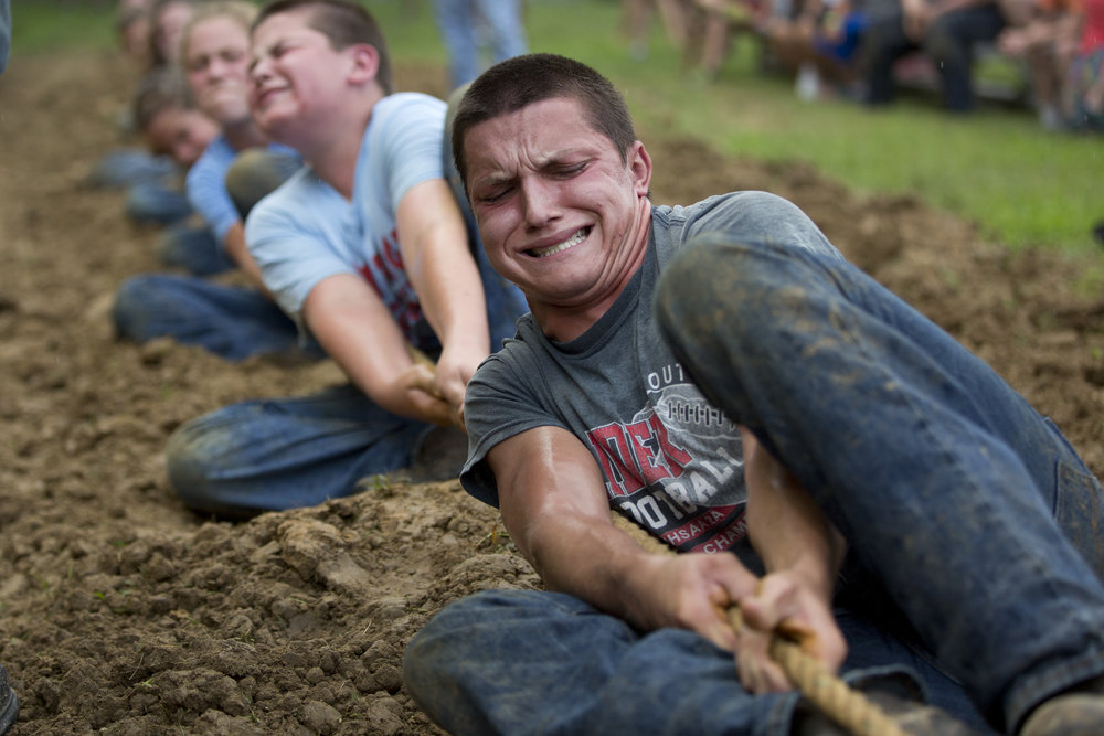 Prestyn Balsmeyer of Huntingburg, 17, grimaced while pulling the rope during the tug-of-war competition at the Dubois County 4-H Fairgrounds in Bretzville on Thursday evening.