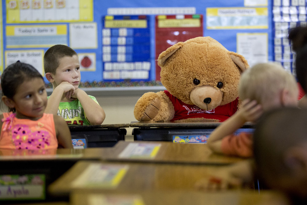 Fifth Street School first-graders Kaylee Ayala, left, and Benny Jones sat next to a bear from the Riley Children's Foundation on Friday. Their classmate, Milagro Alfaro Lopez, recently had open-heart surgery and is recovering at Riley Hospital for Children in Indianapolis. Donated by Speedway, the gasoline and convenience store chain, through the Bear in the Chair program, the bear will sit at Lopez's desk until she returns to school.