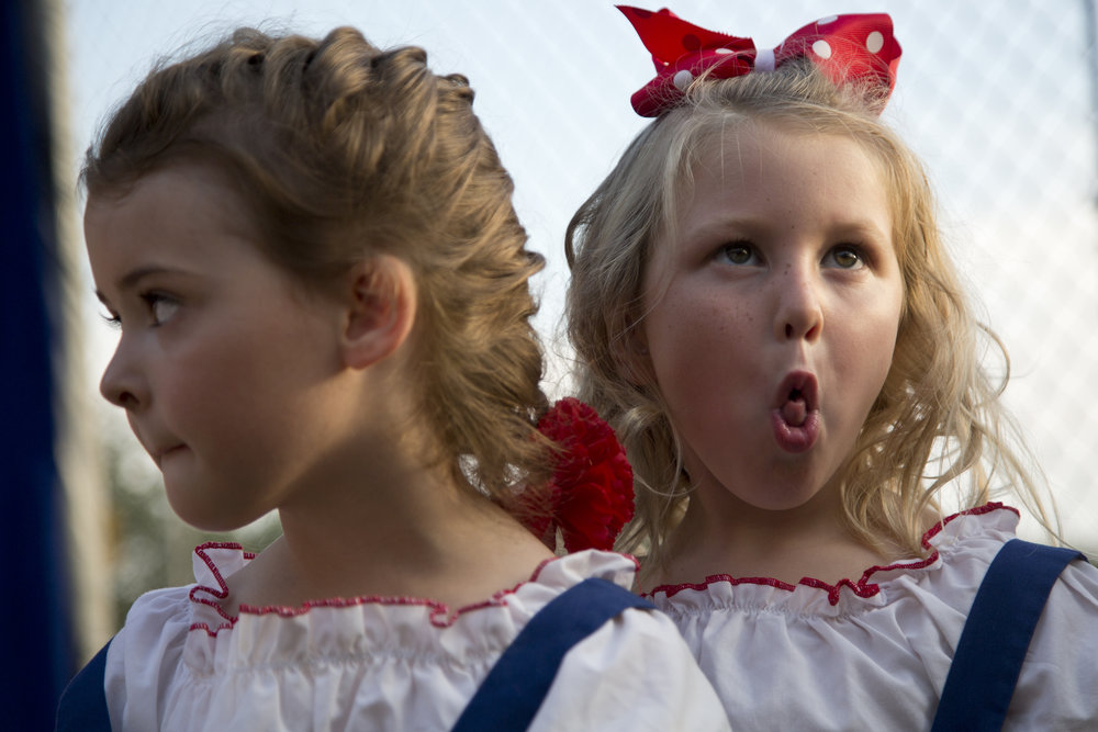 Piper Nichter of Huntingburg, 4, right, rolled her tongue while waiting in line with Madison Richardson of Holland, 5, for the Little Miss and Mister contest to begin during the Holland Community Fest in Holland on Friday. Several parent volunteers asked the girls to make funny faces to help calm their nerves. Piper then showed that she could roll her tongue.