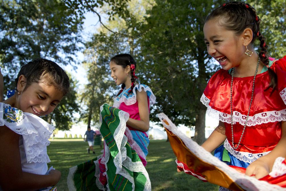 Gabriela Gomez, 6, from left, Jazmin Uresti, 11, and Jaslyn Soto, 8, all of Huntingburg, joked around while waiting to perform a traditional El Salvadoran dance during Latino Fest at Huntingburg City Park in Huntingburg on Saturday.