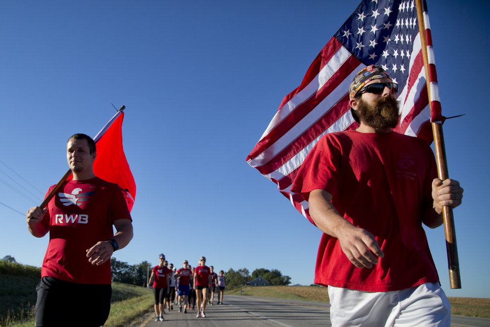 To commemorate the 15th anniversary of the Sept. 11, 2001, attacks, Brandon Schaefer of Ferdinand, left, and Craig Atkins of St. Anthony led more than 30 members of Team Red, White, and Blue on an 11-mile march from Ferdinand to Jasper along State Road 162 on Sunday. Atkins served 12 years as a staff sergeant in the Marine Corps. After each mile, the group stopped to perform nine repetitions of squats. Team Red, White, and Blue is an organization that unites veterans and civilians interested in athletic training.