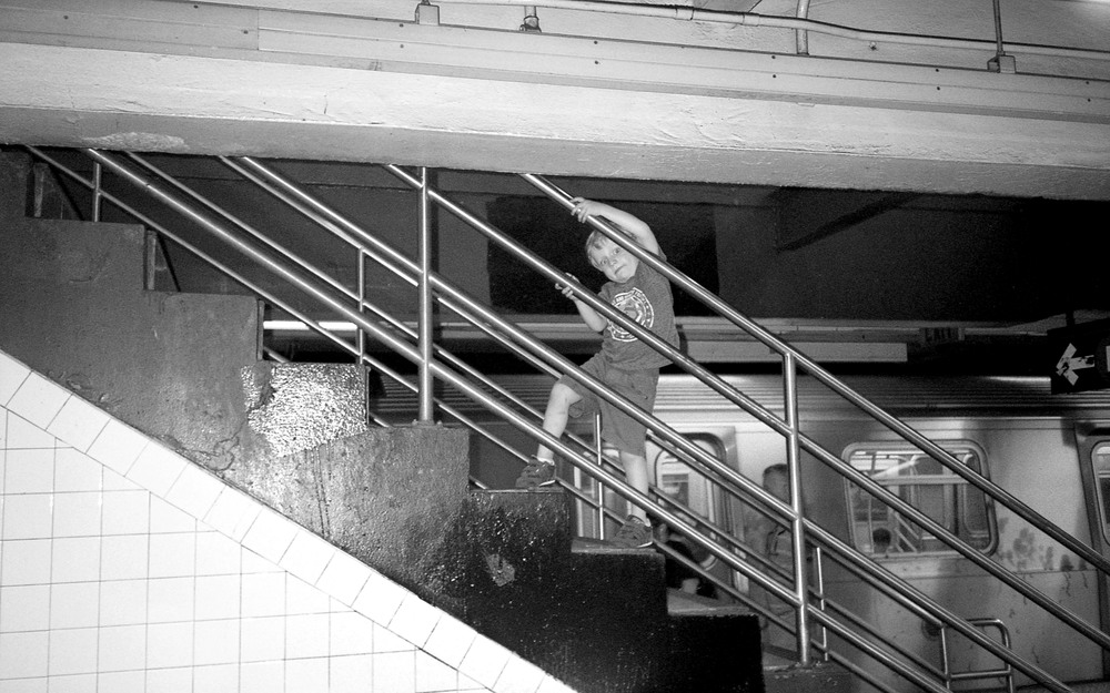 kid playing on subway stairs bw.jpg