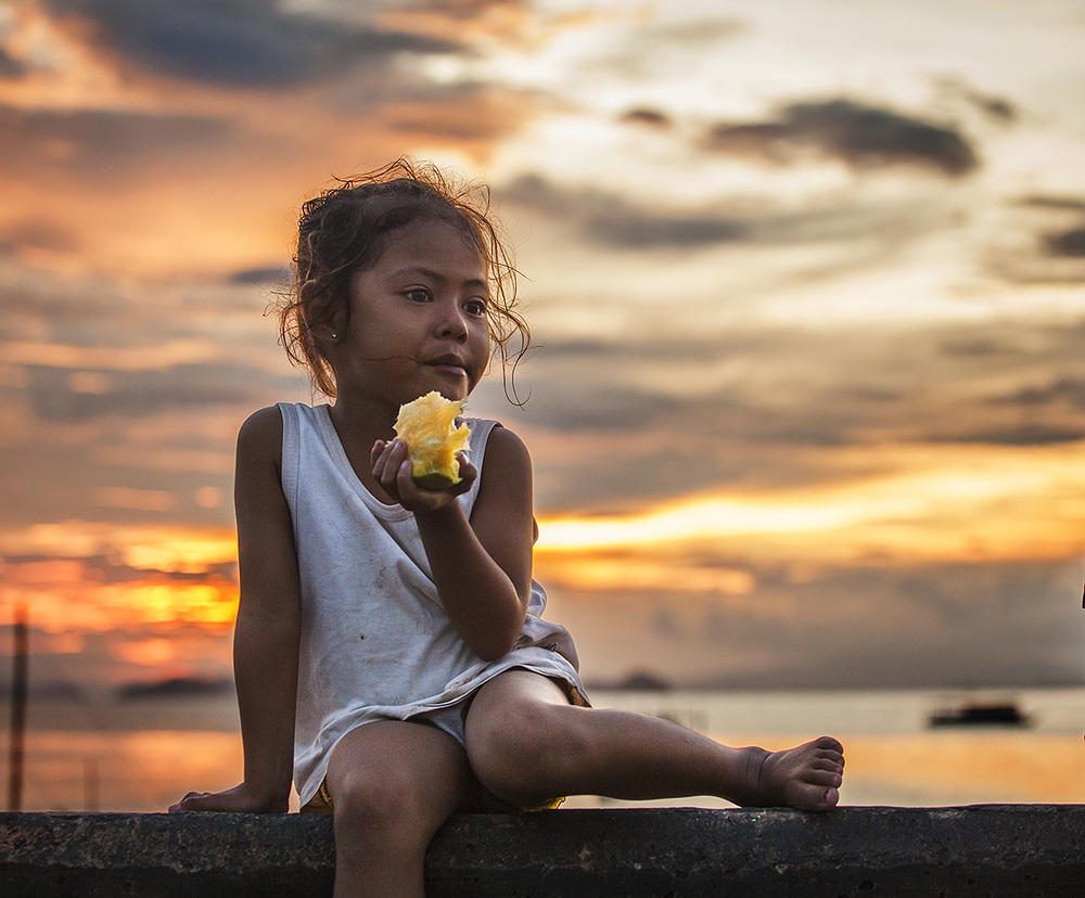 girl eats a mango on the boardwalk of labuan bajo