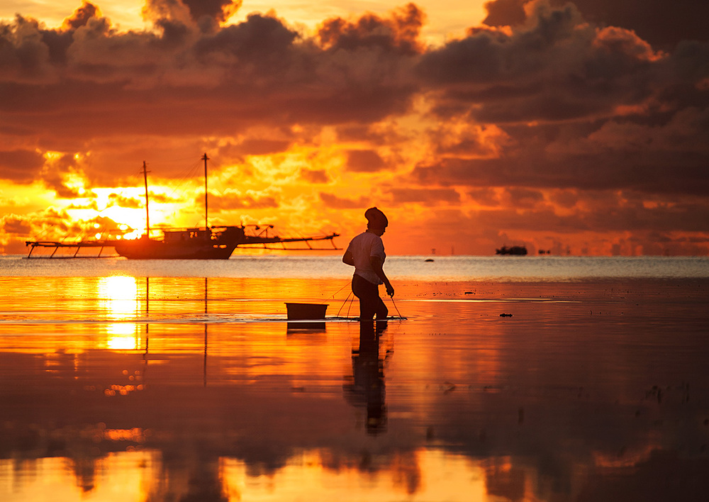 woman collecting clams/seaweed/rocks/who knows at sunrise at the beachside village in Bira