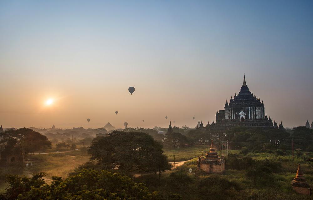 balloons crossing the sky around sunrise