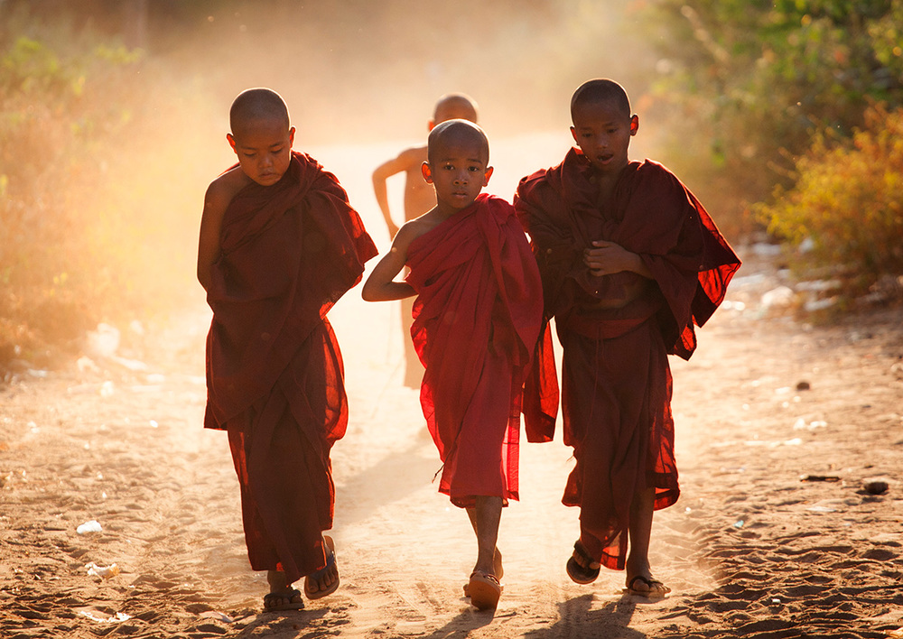 monks walk up a dirt track in a small village