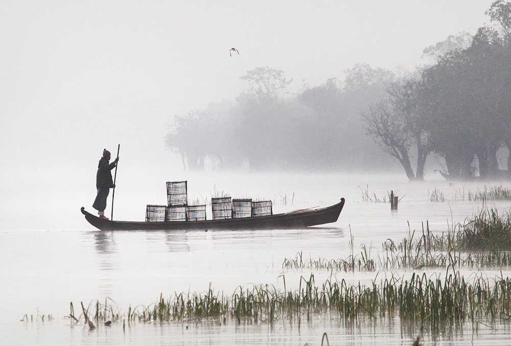 fisherman coming with the fish traps in the early morning fog
