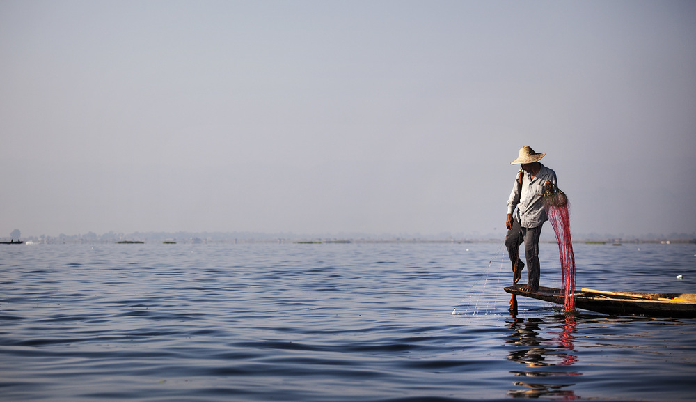fisherman using the distinctive one legged paddling technique