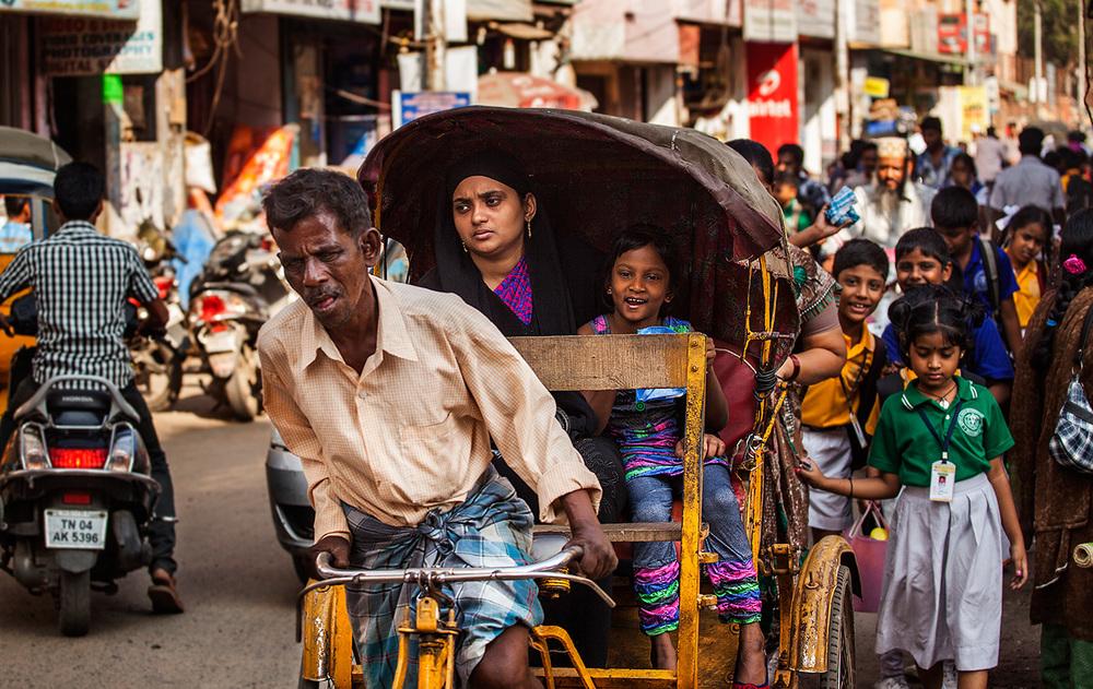 Man working hard cycling his rickshaw
