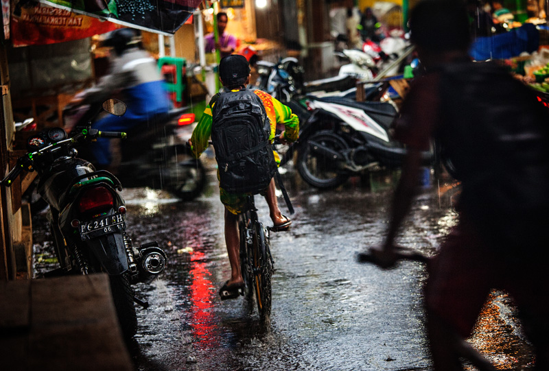 kids riding bikes through the rain in the small town of Sempol