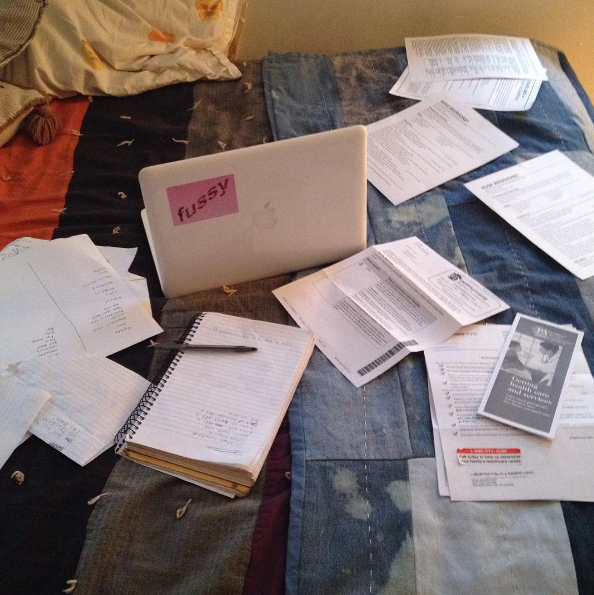 Homework and paperwork spread out on my bed.