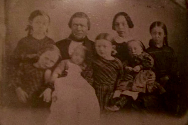 Norman and Jane Rundles with their children. This photo was taken shortly before they left New York by covered wagon for Iowa in 1856.  Norman placed his sister's baby on his lap for the picture, as he wanted a way of visually marking Jane's pregnancy.  Jane was pregnant during their journey by covered wagon and had their first son, named Norman, after his father, soon after they settled on the farm.  Norman Jr. passed away at almost 3 months of age, and one of the pines was planted in his memory.  The other pines were planted for three of the girls, who passed away quite suddenly from an epidemic that swept through the area during the winter of 1865-66.