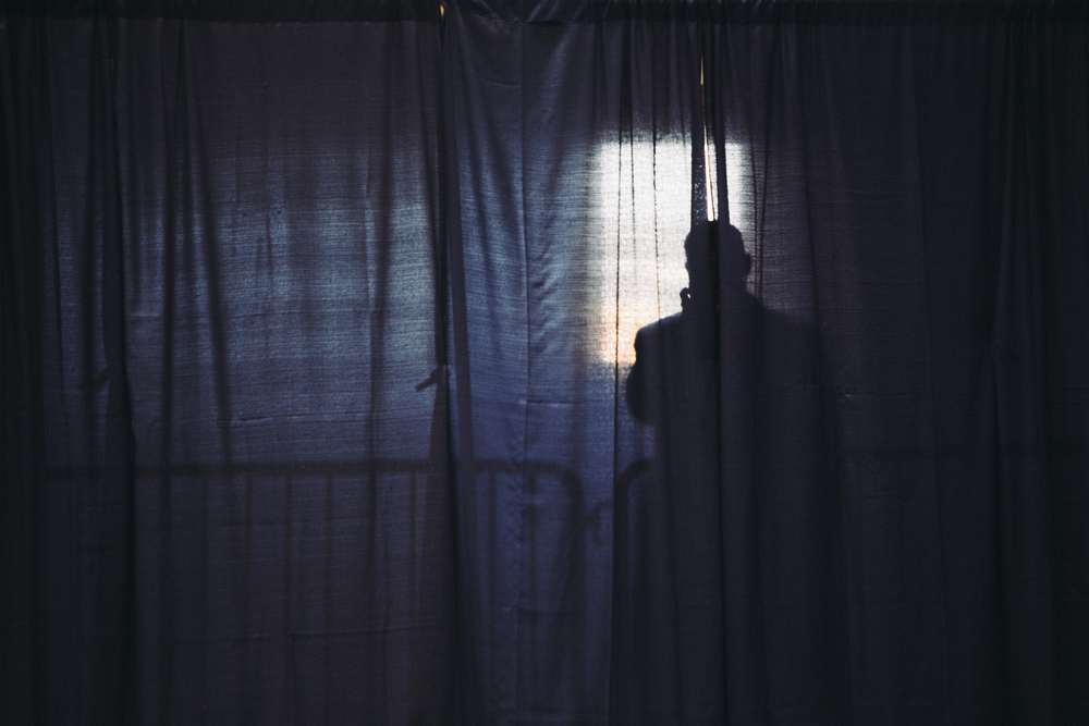 A member of the security detail peers through a curtain as supporters of Congressman (D) Dan Maffei file in to a hangar at Syracuse Hancock International Airport. More than 750 supporters came to hear from Maffei, members of the Syracuse community, and special guest, former president and long-time supporter of Maffeir, Bill Clinton. Dan Maffei is up for reelection in New York's 24th congressional district.