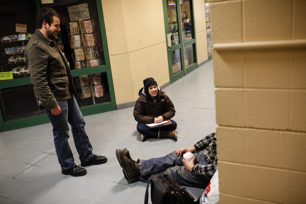 Gary Mann (L), Manager of Outreach and Opportunities at The Rescue Mission of Syracuse and Melissa Marone (C), Housing and Homeless Coalition Coordinator, explain possible alternative living situations to a man named Dale, who spends time during his day at the Regional Transportation Center.