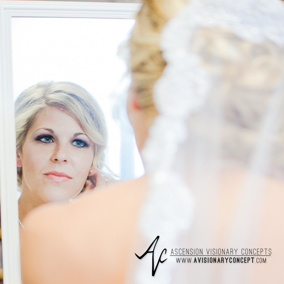 Rochester Wedding Photography Plantation Party House Spencerport Wedding 007 - Bride Getting Dressed Looking in Mirror Lace Edged Veil Stud Earrings.jpg