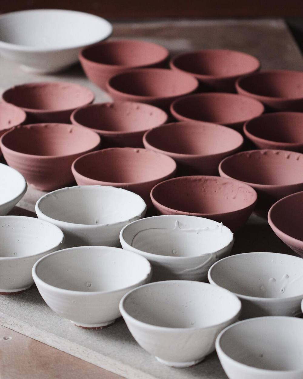 A_portion_of_the_bisque_ware_posted_yesterday_glazed_up._The_white_will_fire_to_a_darker__grey-white__while_the_pinks_behind_will_turn_to_either_a_light_blue_or_dark_green._The_colour_at_this_stage_is_purely_from_the_iron_oxide__which_is_merely_just_.jpg