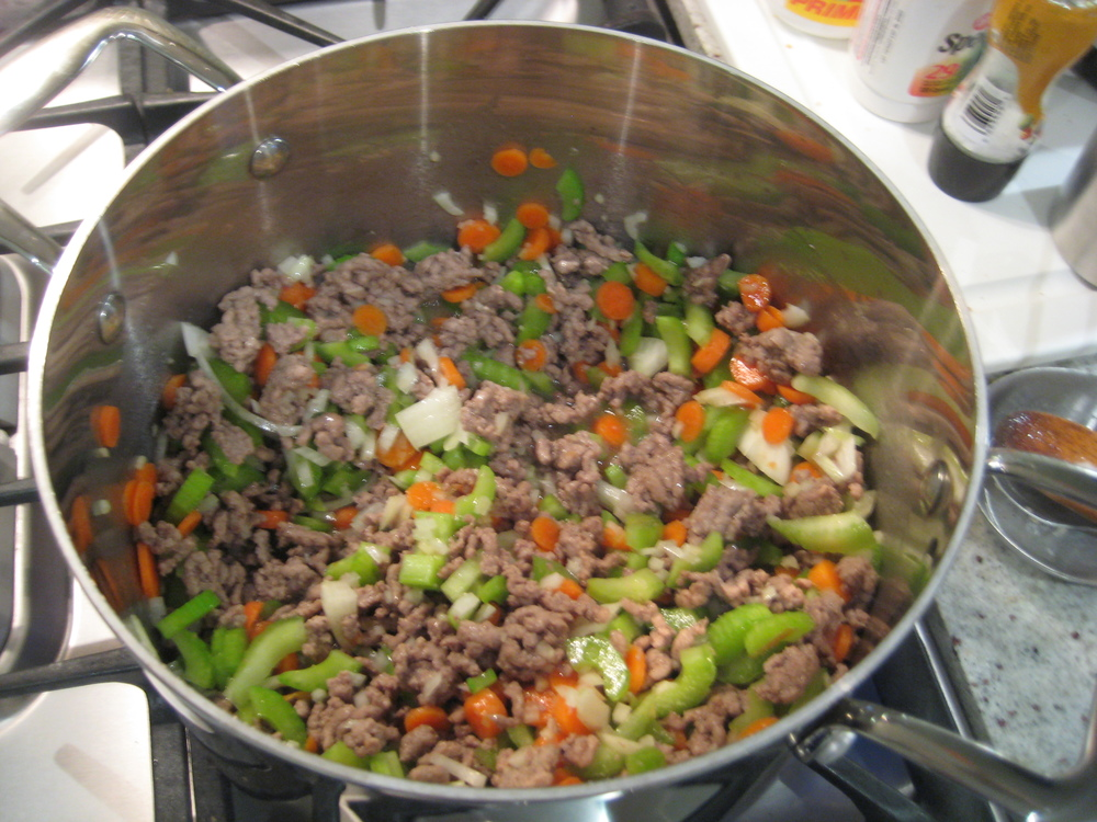 WHEN LAMB IS BROWN, ADD ONIONS, CARROTS, CELERY & 3 TABLESPOONS OF MINCED GARLIC