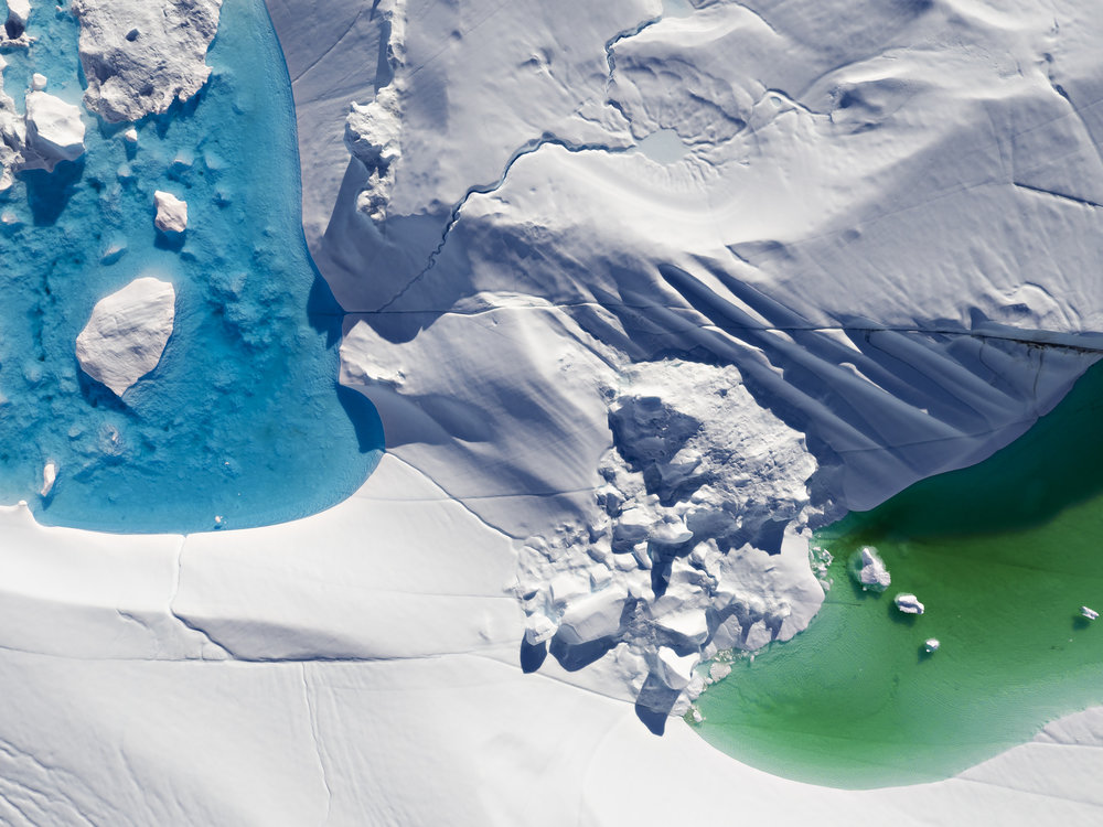 Only by taking to the sky, humans can witness the vibrant colours on the surface of the iceberg.