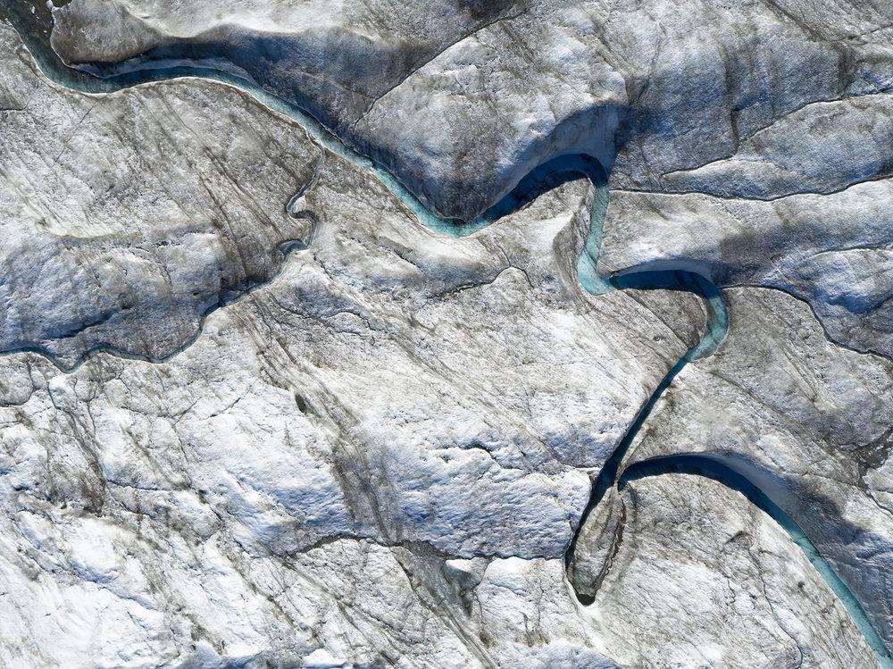 Wie eine Signatur zieht sich der Lauf dieses Schmelzwasserflusses über das Grönländische Inlandeis.