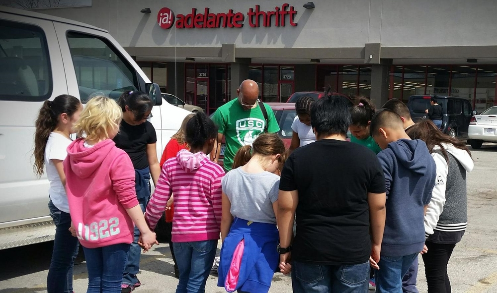 Chuck Allen and youth from the Urban Scholastic Center pray before volunteering at Adelante Thrift.