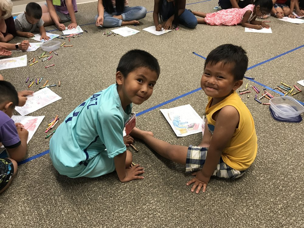 Pictured: A couple of our cute little students coloring at Refuge Kids Club.
