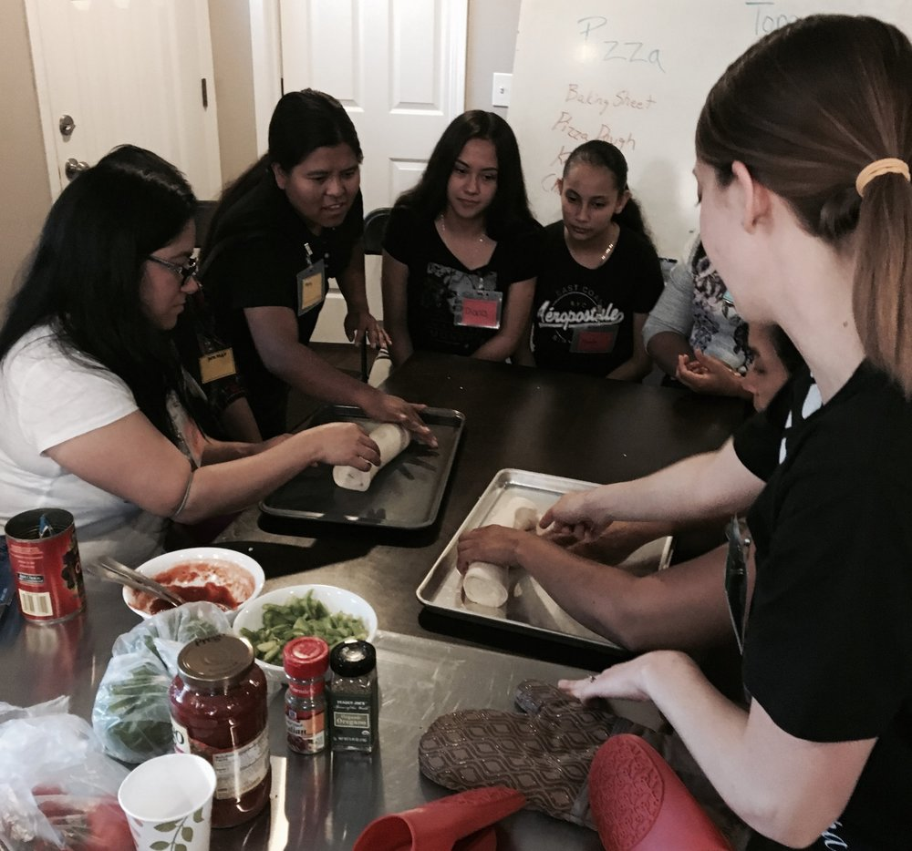 English Club students learning how to make pizza.