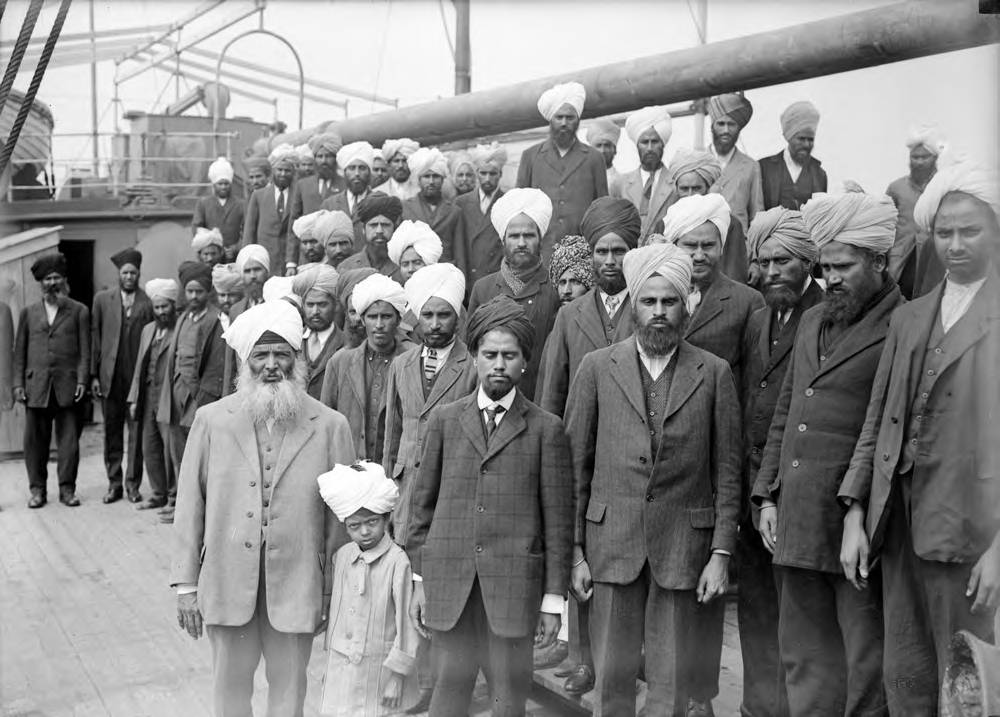 Gurdit Singh Sandhu (man in the left foreground, wearing a white turban) and passengers on board the Komagata Maru.