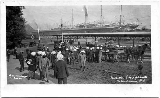 South Asian migrants in the early 1900s loading possessions onto horse drawn wagons at the Canadian Pacific Railway Pier in Vancouver.