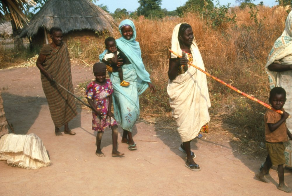 Children leading their parents who have been blinded by onchocerciasis