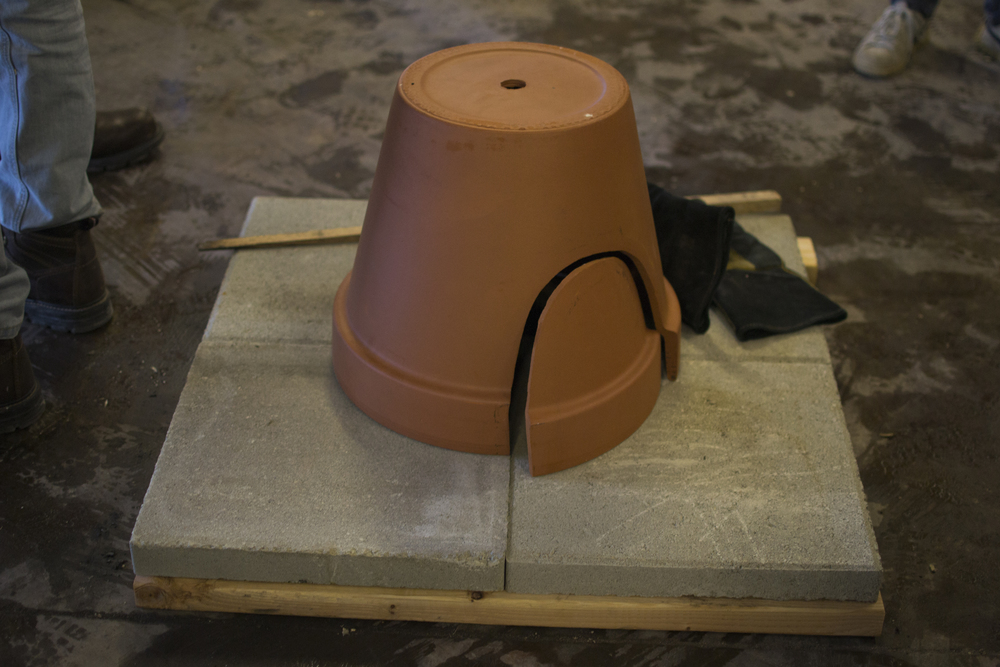 Since we didn't have space for full-fledged earth oven, we created a claypot oven, using the readymade materials of a terra cotta pot and 4 cement pavers. Instructions for this can be found  here .
